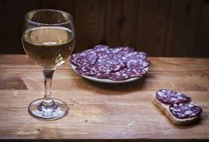 Wine Riesling in a glass . Wine Riesling in a glass and smoked sausage on a plate Royalty Free Stock Images