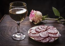 Wine Riesling in a glass . Wine Riesling in a glass and smoked sausage on a plate Royalty Free Stock Photo