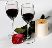 Wine and Roses. Glasses of red wine accompanied by rose and candlelight Stock Photography