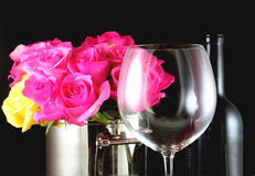 Wine and Roses. Red wine glass and bottle with bouquet of pink and yellow roses royalty free stock photography