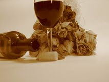 Wine & Roses. Closeup of bouquet of roses with a wine bottle and glass/sepia color picture stock images