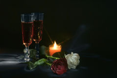 Wine and roses. 2 glasses of wine on the black background, candle and red and white roses Stock Photo