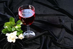 Wine and Roses. Red wine with white roses on black satin velvet Royalty Free Stock Photography