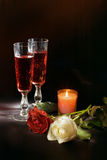 Wine and roses. Two glasses with wine, roses and a burning candle on a black background Royalty Free Stock Photography