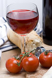 Wine rustic lunch. A tasty rustic platter of french bread, vine tomatoes and red wine royalty free stock photography