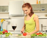 Wine and salad. Attractive woman preparing food in the kitchen Royalty Free Stock Photos