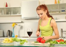 Wine and salad. Attractive woman preparing food in the kitchen Stock Photos