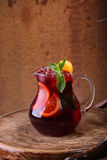 Wine of Sangrija with an orange in a transparent jug on a wooden. Table royalty free stock photography