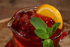 Wine of Sangrija with an orange in a transparent jug on a wooden. Table stock image