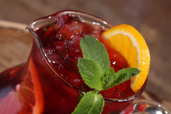 Wine of Sangrija with an orange in a transparent jug on a wooden. Table stock photography