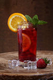 Wine of Sangrija in a transparent glass with a strawberry, an or. Ange and mint on a wooden table stock images
