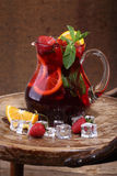 Wine of Sangrija in a transparent jug with a strawberry, an oran. Ge, mint and ice cubes on a wooden table royalty free stock photography