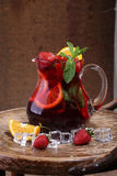 Wine of Sangrija in a transparent jug with a strawberry, an oran. Ge, mint and ice cubes on a wooden table stock images