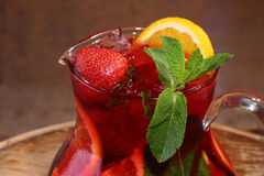 Wine of Sangrija in a transparent jug with a strawberry, an oran. Ge, mint and ice cubes on a wooden table stock photo