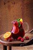 Wine of Sangrija in a transparent jug on a wooden table with an. Orange and a strawberry royalty free stock image