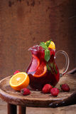 Wine of Sangrija in a transparent jug on a wooden table with an. Orange and a strawberry stock images