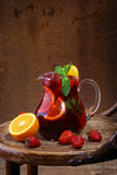 Wine of Sangrija in a transparent jug on a wooden table with an. Orange and a strawberry royalty free stock photo