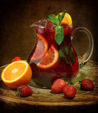 Wine of Sangrija in a transparent jug on a wooden table with an. Orange and a strawberry royalty free stock photos