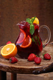 Wine of Sangrija in a transparent jug on a wooden table with an. Orange and a strawberry stock image