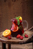 Wine of Sangrija in a transparent jug on a wooden table with an. Orange and a strawberry stock photos
