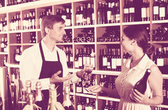 Wine seller and customer in wine shop. Friendly smiling male seller  helping to choose wine to female customer in wine shop Royalty Free Stock Photos