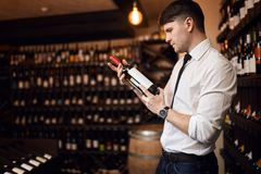 Wine seller holding a bottle of wine stock images