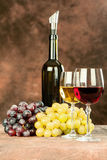 Wine set. Wine bottle near shiny wine cups and grape Royalty Free Stock Photography
