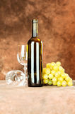 Wine set. Wine bottle and shiny wine cup near grape Royalty Free Stock Image