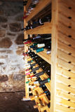 Wine shelves. Collection of fine wine bottles arranged on wood shelves Royalty Free Stock Image