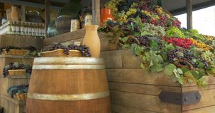Wine Shop. Barrel, carboy, bottle of wine and grapes on wooden shelf stock video