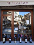 WINE SHOP IN CORTONA, ITALY. Cortona, Italy - October 30, 2014: Wine bottles on the window of a wine shop in the Piazza della Repubblica, the main square in Royalty Free Stock Image