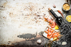 Wine with shrimp and spices. Fresh seafood. Wine with shrimp and spices with a fishing net. On rustic background Royalty Free Stock Photo
