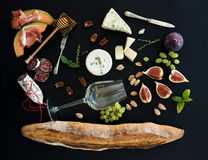 Wine and snack set. Baguette, glass of white, figs Stock Photos