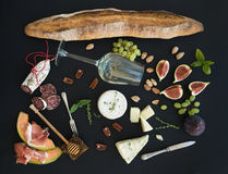 Wine and snack set. Baguette, glass of white, figs, grapes, nuts, cheese variety, meat appetizers, herbs on black grunge Royalty Free Stock Photography