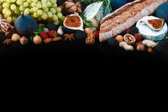 Wine and snack set. Baguette, white, figs, grapes, nuts, cheese variety, meat appetizers and herbs Frame isolated on black stock photos
