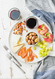 Wine snack set. Cheese, chicken carpaccio, mediterranean olives, fruits, nuts and two glasses of red on ceramic plate royalty free stock photo