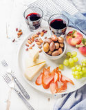 Wine snack set. Cheese, chicken carpaccio, mediterranean olives, fruits, nuts and two glasses of red on ceramic plate Stock Images