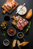 Wine snack set. Glass of red, meat selection, mediterranean olives, sun-dried tomatoes, baguette slices, camembert Stock Photo