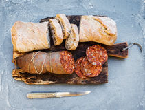 Wine snack set. Hungarian mangalica pork salami sausage and rustic bread on dark wooden board over a rough grey-blue Stock Image