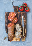 Wine snack set. Hungarian mangalica pork salami sausage, rustic bread and fresh tomatoes on dark wooden board over a Stock Photo