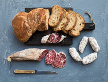 Wine snack set. Italian slami sausages and rustic bread on dark wooden board over a rough grey-blue concrete background Stock Images