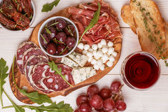 Wine snack set. Variety of cheese and meat, olives, grapes, arug Royalty Free Stock Photo