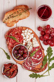 Wine snack set. Variety of cheese and meat, olives, grapes, arug Stock Image