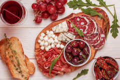 Wine snack set. Variety of cheese and meat, olives, grapes, arug Royalty Free Stock Photography