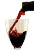 Wine som häller från, buteljerar in i ett exponeringsglas. Arkivbild
