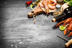 Wine with spice and fresh shrimp, lobster. The preparation of fresh seafood. Wine with spice and fresh shrimp, lobster. On a black chalkboard Royalty Free Stock Photos