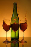 Wine splash. Green bottle with three drinks on the mirrow surface royalty free stock photo