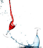 Wine splashing in glasses. Abstract background of red and blue wine splashing and spilling in wine glasses with white background and copy space Royalty Free Stock Photos