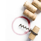 Wine stain. Wine corks, small corkscrew and round, red wine stain on white table cloth Stock Image