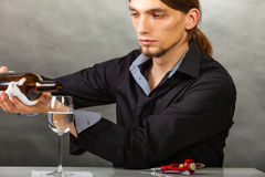 Wine steward fills glass. Alcohol liquor drinking tasting relax concept. Wine steward fills glass. Young male waiter pours drink into cup Stock Photos